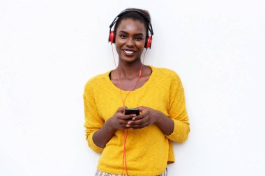 Portrait of smiling young woman listening to music with headphones and mobile phone against isolated white background