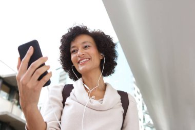 Close up portrait of smiling african american woman listening to music with headphones and mobile phone