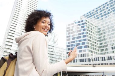 Side portrait of happy african american woman holding mobile phone in the city