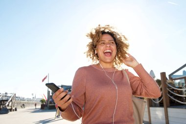 Portrait of happy african american woman listening to music with mobile phone and headphones