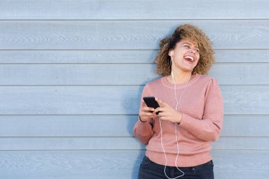Portrait of carefree woman laughing with earphones and mobile phone against gray background