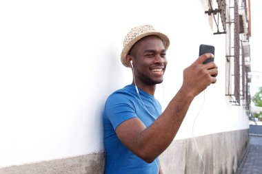 Portrait of happy african american man listening to music with mobile phone and earphones