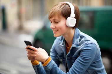 Close up portrait of young woman smiling with mobile phone and headphones