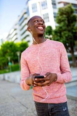 Portrait of happy young african man listening to music with cellphone and headphones