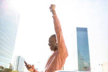 Portrait of happy young black man punching the air while looking at mobile phone
