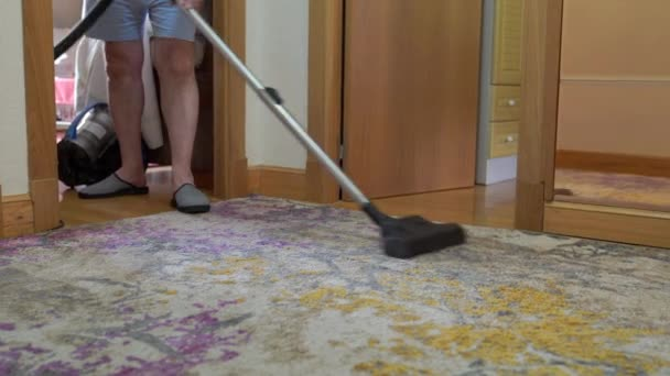 Neznámý muž čistící koberec s vysavačem