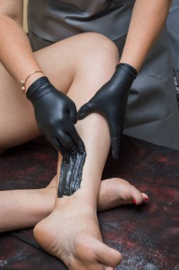 woman doing sugaring your legs at the beauty salon