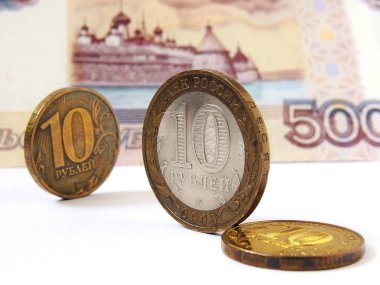 Russian coins of 10 rubles are on the background of a banknote of 500 rubles. One of the coins is commemorative bimetallic. News about the state budget, the central bank and the refinancing rate. Close-up