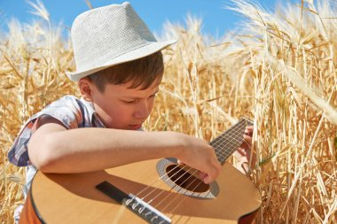 child with guitar is in the yellow wheat field, bright sun, summer landscape