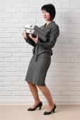 geschäftsfrau mit Ordner, bekleidet mit einem grauen Anzug Posen vor einer weißen Wand
