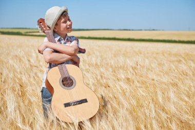 child boy with guitar is in the yellow wheat field, bright sun, summer landscape