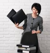 Fotografie geschäftsfrau mit Ordner, bekleidet mit einem grauen Anzug Posen vor einer weißen Wand