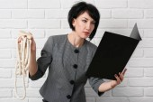 Fotografie angry business woman with laptop and folders having stress, dressed in a gray suit poses in front of a white wall
