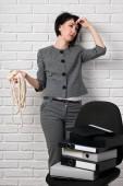 wütend Business-Frau mit Laptop und Ordner, die mit Stress, gekleidet in einem grauen Anzug Posen vor einer weißen Wand