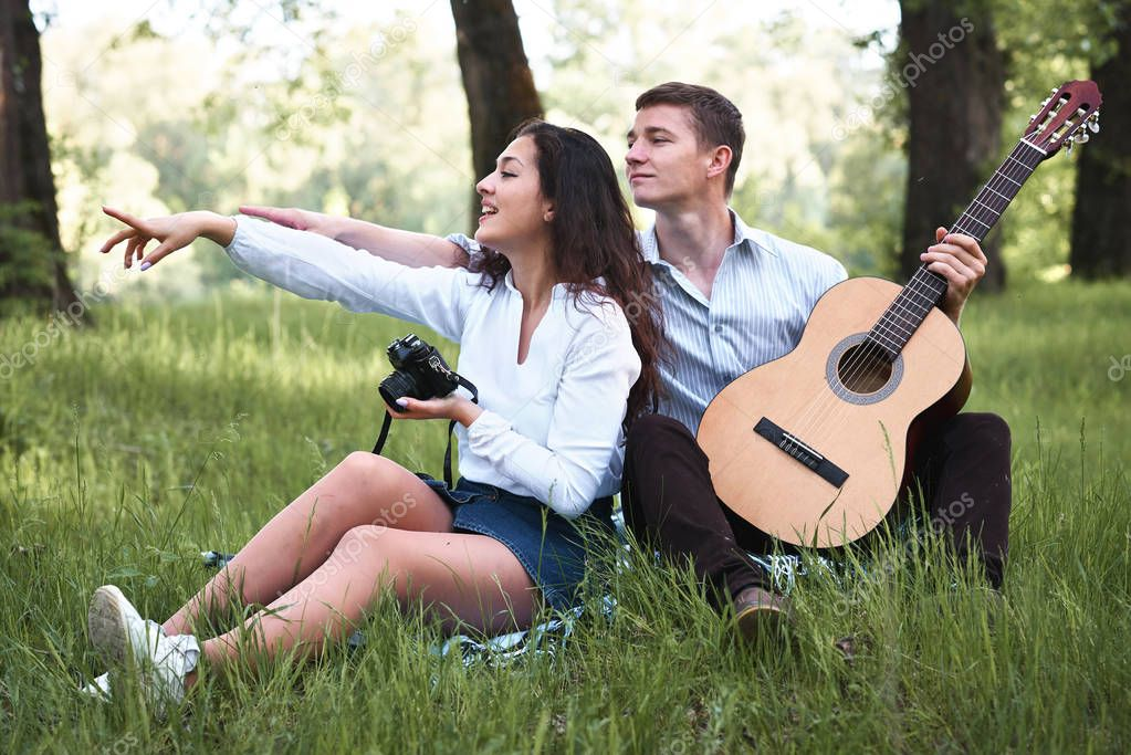 young couple walking in the forest and playing guitar, taking photo on old camera, summer nature, bright sunlight, shadows and green leaves, romantic feelings