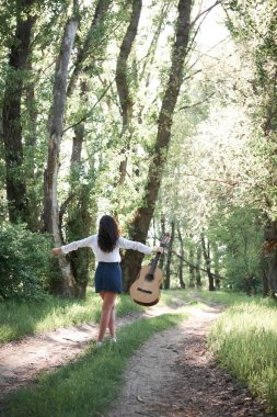 young woman walking in the forest and playing guitar, summer nature, bright sunlight, shadows and green leaves, romantic feelings