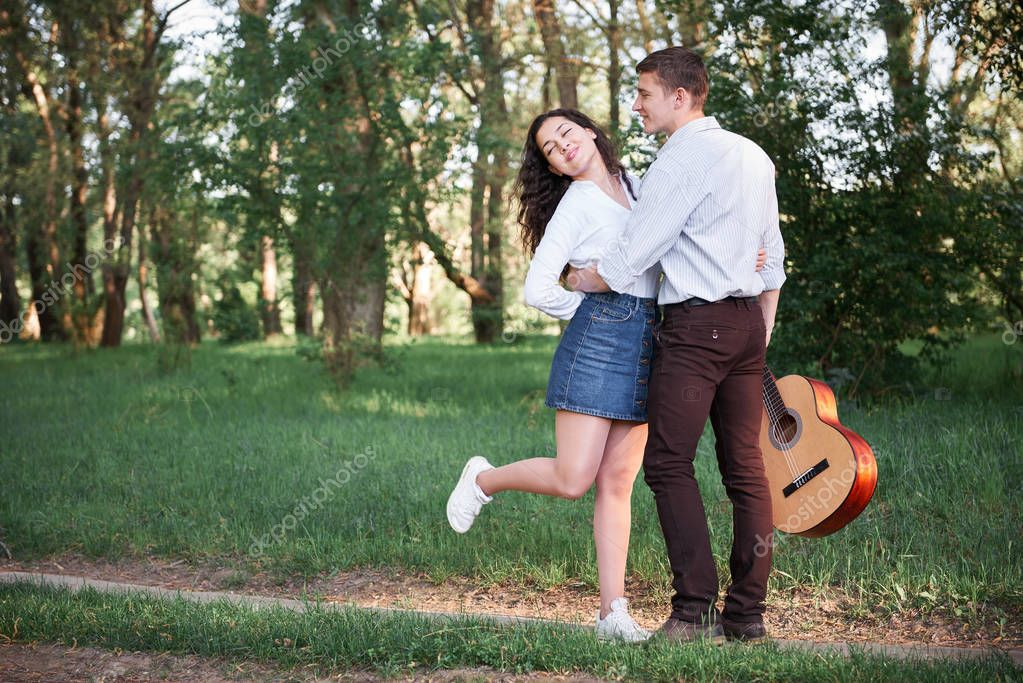 young couple walking in the forest and playing guitar, summer nature, bright sunlight, shadows and green leaves, romantic feelings