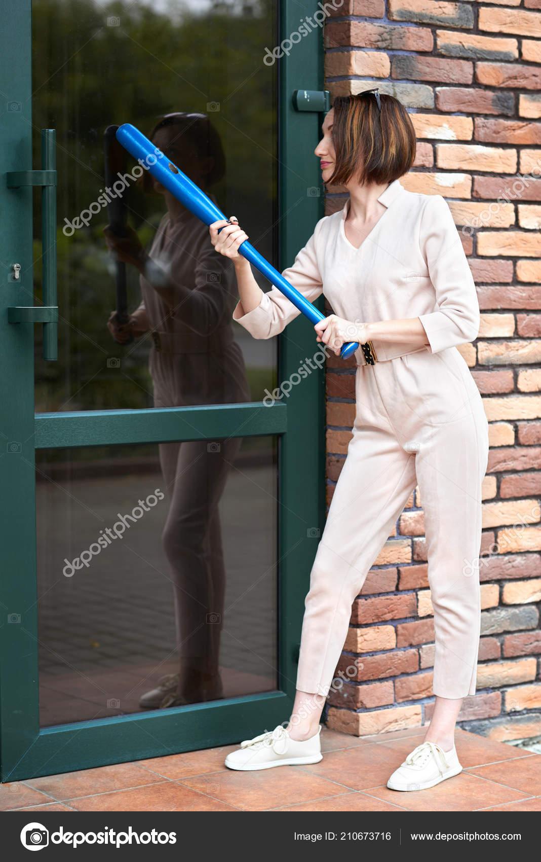 433f854ebf0e6 A garota está à porta fechada da loja e tenta terminar com um taco de  beisebol– imagens de bancos de imagens