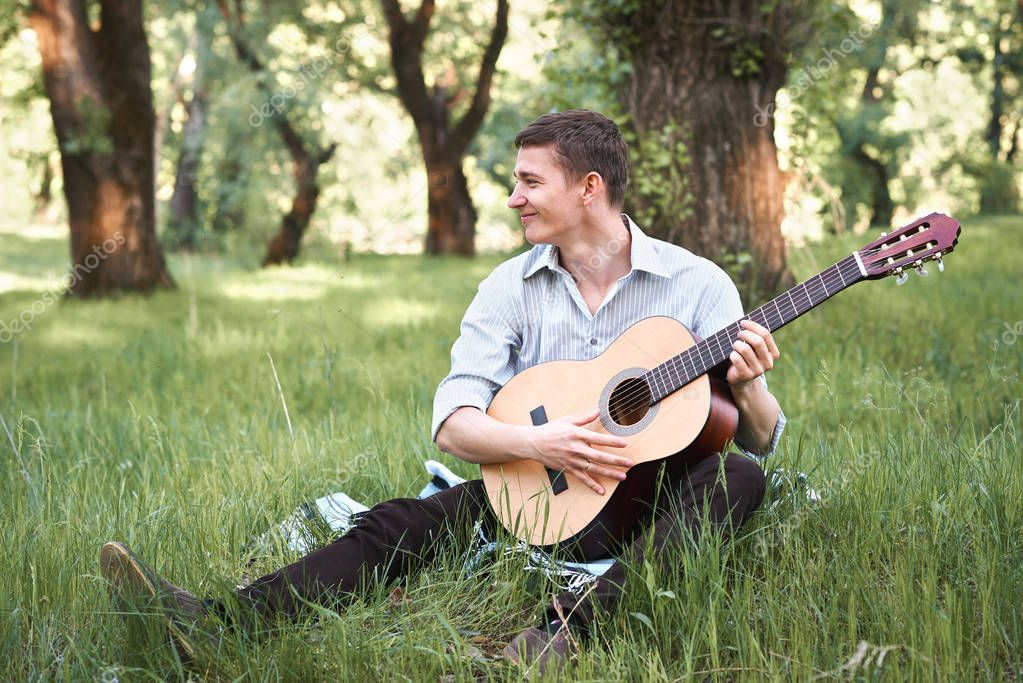 young man playing guitar in the forest, sit on the grass, summer nature, bright sunlight, shadows and green leaves, romantic feelings