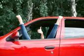 fiatal nő vezető pihen egy piros autó, rátette a lábát a kocsiját az ablakot, és intett, boldog utazik fogalom