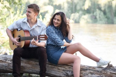 young couple sitting on a log by the river and playing guitar, summer nature, bright sunlight, shadows and green leaves, romantic feelings