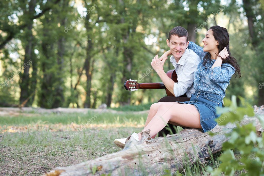 young couple sitting on a log in the forest and playing guitar, summer nature, romantic feelings