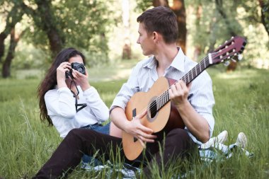 young couple sitting in the forest and playing guitar, taking photo on old camera, summer nature, bright sunlight, shadows and green leaves, romantic feelings
