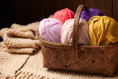 colorful wool threads for knitting in basket, wooden background