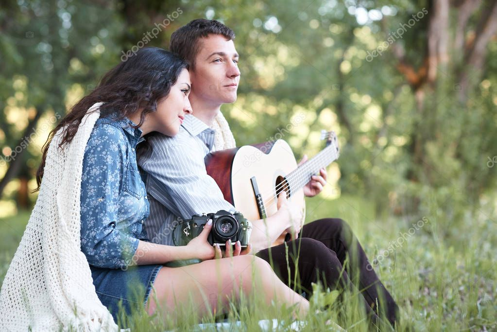 young couple sitting in the forest and playing guitar, summer nature, bright sunlight, shadows and green leaves, romantic feelings
