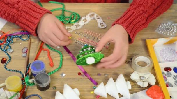 Dítě dívka dělá dekorace pro dovolenou. Řemesla a hračky, vánoční stromeček a další. Malování akvarelů. Pohled shora. Kresby pracoviště s kreativní doplňky. Nástroje pro ploché laických umění