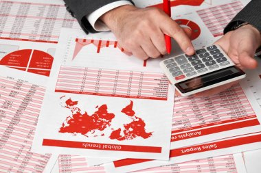 Businessman accountant using calculator for calculating finance on desk office. Business financial accounting concept Red reports and graphs. Office employee examines schedules and reports.