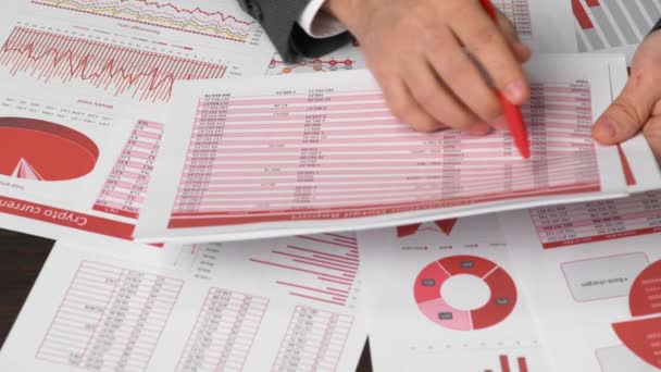 Businessman accountant using calculator for calculating finance on desk office. Business financial accounting concept. Red reports and graphs. Office employee examines schedules and reports.