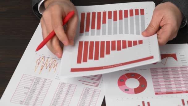 Podnikatel účetní pomocí kalkulačky pro výpočet penále na stůl kancelářský. Finanční účetní koncepce. Červené zprávy a grafy. Zaměstnanec úřadu zkoumá plány a zprávy