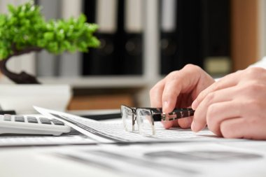 Businessman working in office and calculating finance. He takes glasses. Business financial accounting concept.