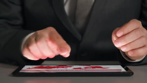Businessman working on a tablet, analyzes the graphs and tables, hands closeup.
