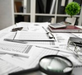 Büroinnenraum-die Tabelle mit Dokumenten, Berichten und Regalen mit Ordner. Konzept der Finanzbuchhaltung.