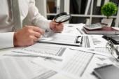 Geschäftsmann arbeitet im Büro und berechnet Finanzen, liest und schreibt Berichte. Konzept der Finanzbuchhaltung.