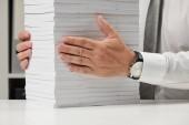 Geschäftsmann, der in einem Büro arbeitet, liest stapelweise Bücher und Berichte. Finanzbuchhaltungskonzept für Unternehmen.