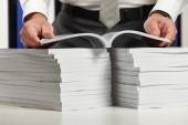 Geschäftsmann arbeitet in einem Büro, liest Stapel von Büchern und Berichten. Business Financial Accounting Konzept.