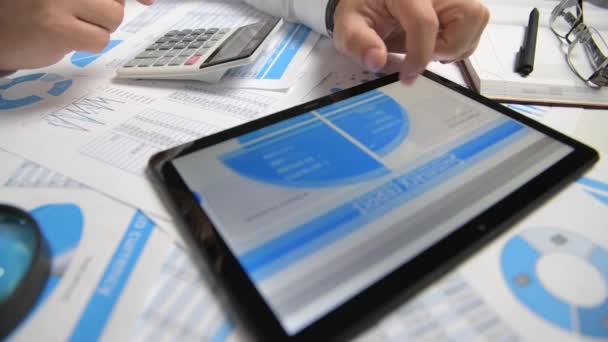 Businessman working with tablet pc, calculating, reading and writing reports. Office employee, table closeup. Business financial accounting concept.
