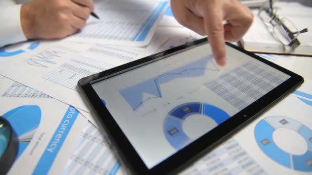 Geschäftsmann arbeitet und berechnet, liest und schreibt Berichte. Mit Tablet-PC. Büromitarbeiter, Tabellennahaufnahme. Business Financial Accounting Konzept.