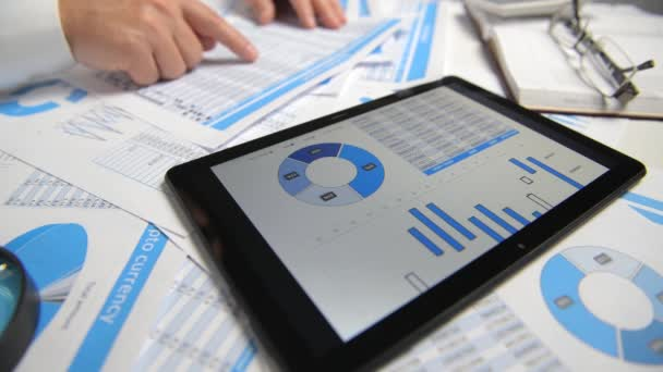 Businessman working and calculating, reads and writes reports. Using tablet pc. Office employee, table closeup. Business financial accounting concept.