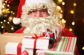 Mikulás pózol sok ajándékot, ül fedett közelében díszített karácsonyfa fények - Boldog Karácsonyt és Boldog Ünnepeket!