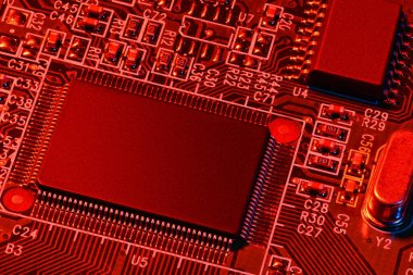 printed circuit board and microchip, or cpu, in red light closeup - electronic component for digital equipment, concept for development of electric computer circuits