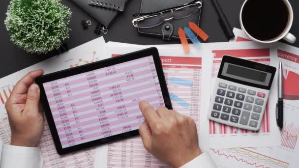 Top kilátás üzletember kezét dolgozik tabletta pc és pénzügyi beszámolók. Modern fekete íróasztal, jegyzetfüzettel, ceruzával és sok mindennel. Lapos terítőasztal elrendezése.