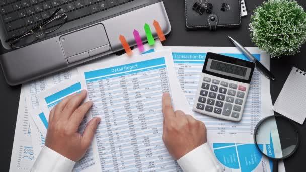 Pohled shora na ruce podnikatele, kteří pracují s tabletem PC a finanční zprávy. Moderní černý kancelářský stůl s poznámkovým blokem, tužkou a spoustou dalších věcí. Ploché rozložení stolu.