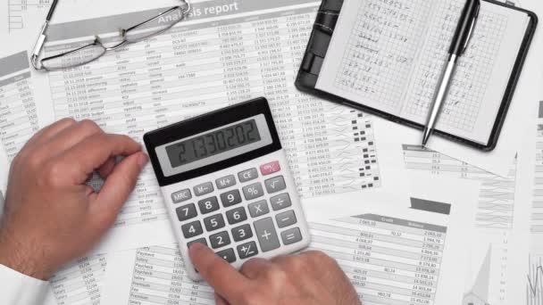 Špičkový pohled na podnikatele, který pracuje s účetními výkazy. Moderní černý kancelářský stůl s notebookem, kalkulačkou, perem a spoustou dalších věcí. Ploché rozložení stolu.