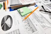 Top pohled na kancelářský stůl - práce s finančními zprávami, analýzami a účetnictvím, stoly a grafy, různé kancelářské položky pro vedení účetnictví