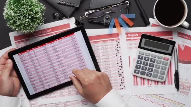 Az üzletember pénzügyi kimutatásokkal dolgozik. Modern fekete íróasztal, jegyzetfüzettel, kalappal, tollal és sok mindennel. Lapos terítőasztal elrendezése.