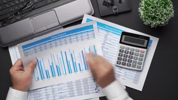 Top view of businessman working with financial statements. Modern office desk with notebook, calc, pen and a lot of things. Flat lay table layout.